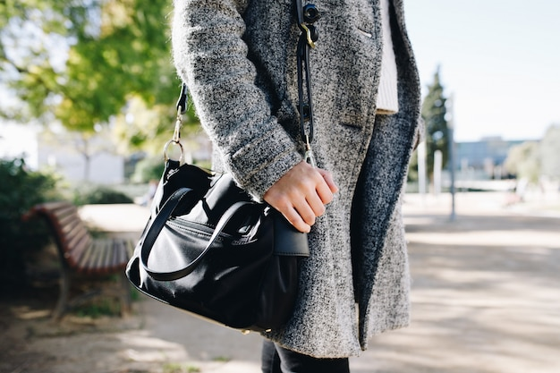 Woman wearing and posing with a coat and purse in autumn collection
