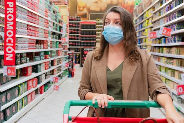 쇼핑 카트와 보호 마스크를 착용하는 여자가 가까이, 제품 설명을 확인