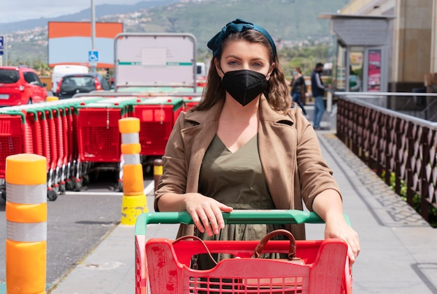쇼핑 카트 야외 쇼핑몰 보호 마스크를 착용하는 여자