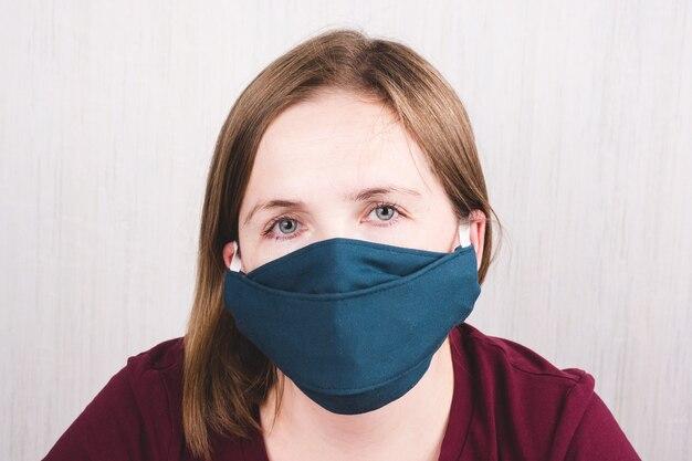 코로나 바이러스에 대한 보호 수제 얼굴 마스크를 착용하는 여자. 코로나 바이러스 예방 장비