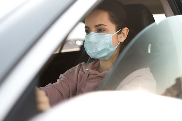 Woman wearing protection mask in car