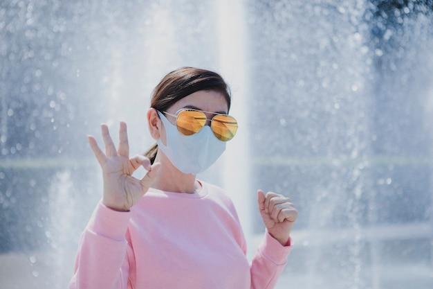 健康のために屋外で手を上げる保護マスクを身に着けている女性