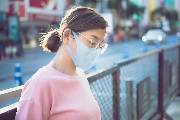屋外に立っている保護マスクを身に着けている女性