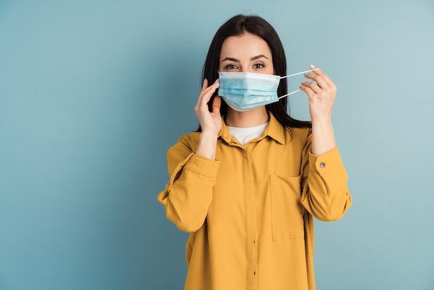 青い壁に保護医療マスクを着用している女性