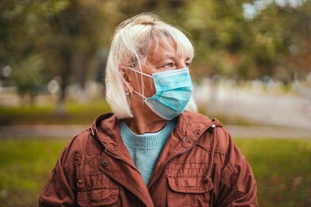 Женщина в защитной маске и теплом кашемировом шарфе в парке на открытом воздухе во время карантина ...