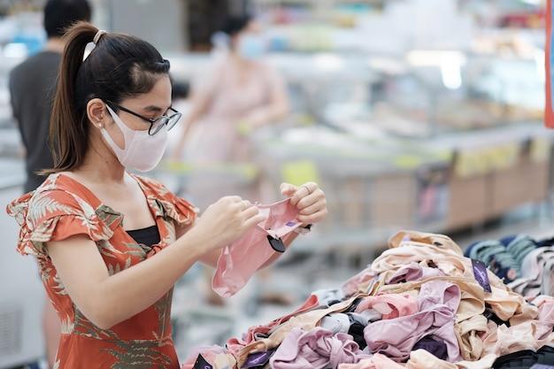 防護マスクを着用し、食料品店やデパートで買い物をする女性