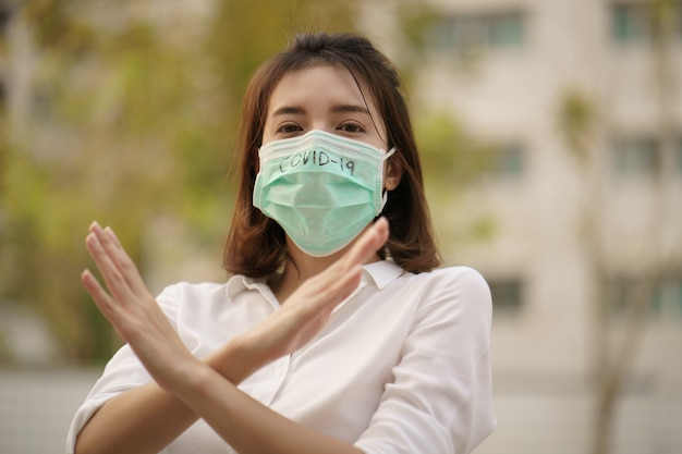 Woman wearing protective mask corona virus (covid-19) text written crossed her arms stop sign.