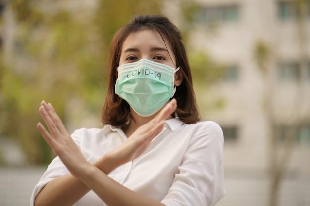 書かれた防護マスクコロナウイルス(covid-19)のテキストを身に着けている女性は、彼女の腕の一時停止の標識を越えました。