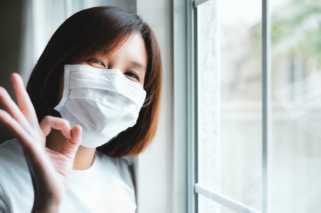 Женщина в защитной маске делает жест у окна