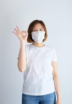 손으로 확인 사인을 하 고 보호 마스크를 착용 해 여자