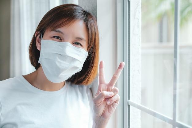 Женщина в защитной маске делает жест победы у окна
