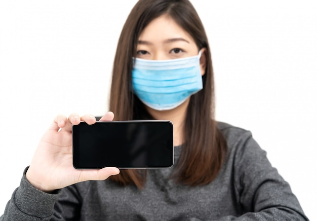 携帯電話を押しながら示す防護マスクを着ている女性