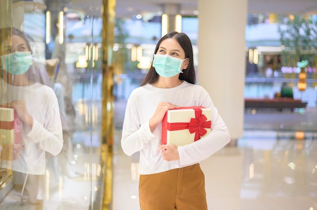 A woman wearing protective mask holding a gift box in shopping mall, shopping under covid-19 pandemic