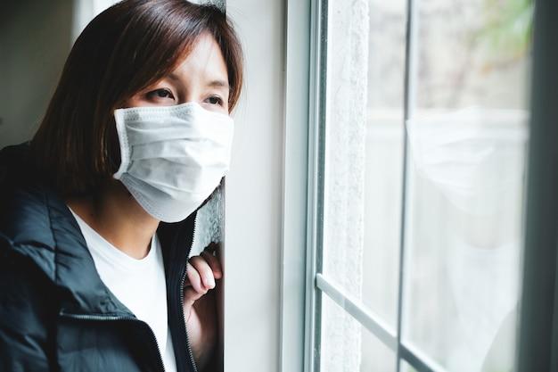 창문을 통해보고 보호 마스크를 착용 해 여자