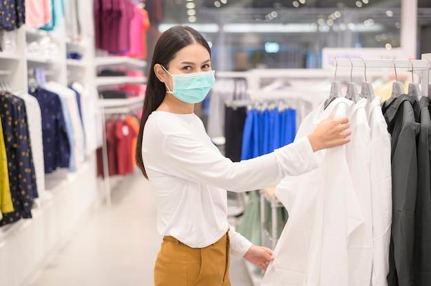 Женщина в защитной маске делает покупки в условиях пандемии covid-19 в торговом центре