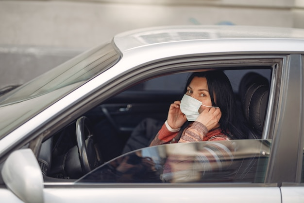 Woman wearing a protective mask sitting in a car