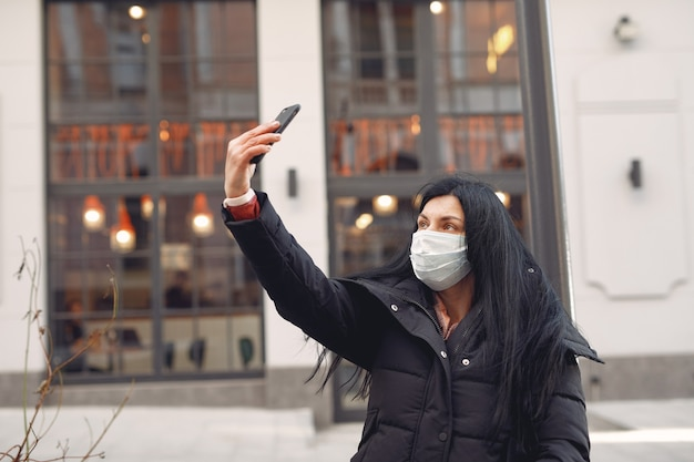 Woman wearing a protective mask sitting on the street taking a selfie