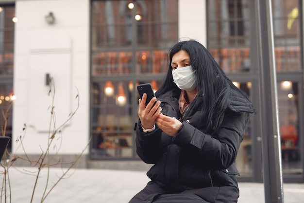 Woman wearing a protective mask sitting on the street using mobile phone
