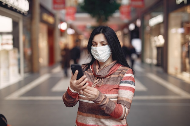 Woman wearing a protective mask using a mobile phone