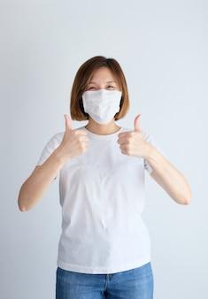 엄지 손가락으로 보호 마스크를 착용 해 여자
