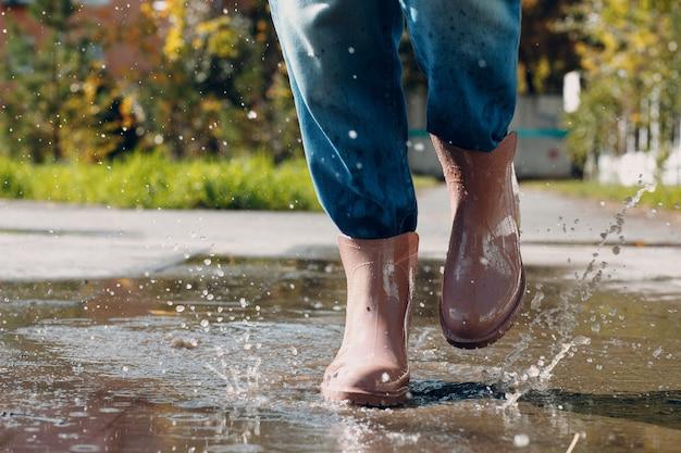 Женщина в резиновых сапогах от дождя идет, бежит и прыгает в лужу с брызгами и каплями воды в осенний дождь
