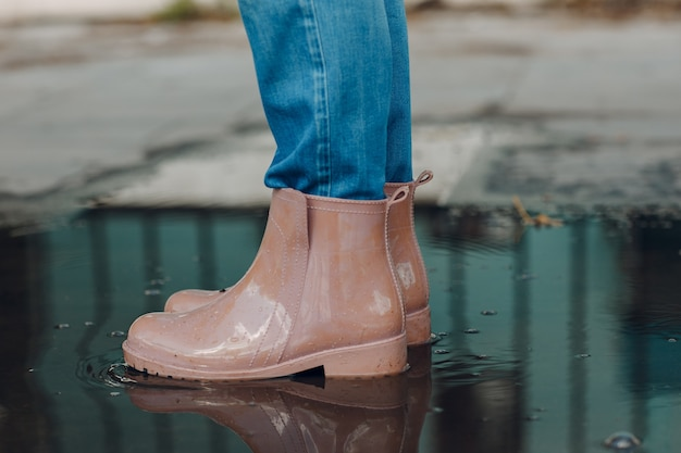 Woman wearing rain rubber boots walking running and jumping into puddle with water splash and drops in autumn rain.