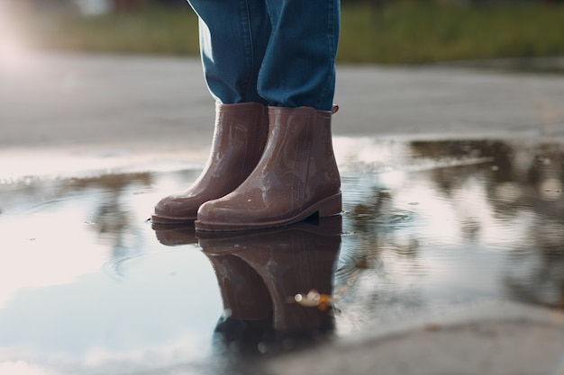 Woman wearing rain rubber boots walking running and jumping into puddle with water splash and drops ...