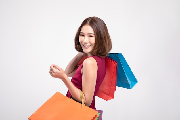 Woman wearing red dress smiles holding shopping bags