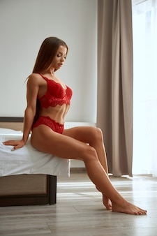 Woman wearing red lace lingerie posing on bed