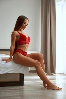 Женщина в красном кружевном нижнем белье позирует на кровати