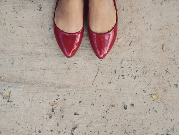 Woman wearing red leather shoes ballerinas standing on gray concrete floor.