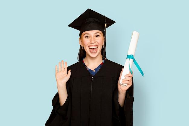 Donna che indossa insegne mentre tiene la sua laurea per la laurea