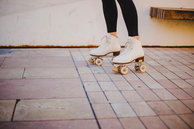 Woman wearing rollerskates riding on pavement