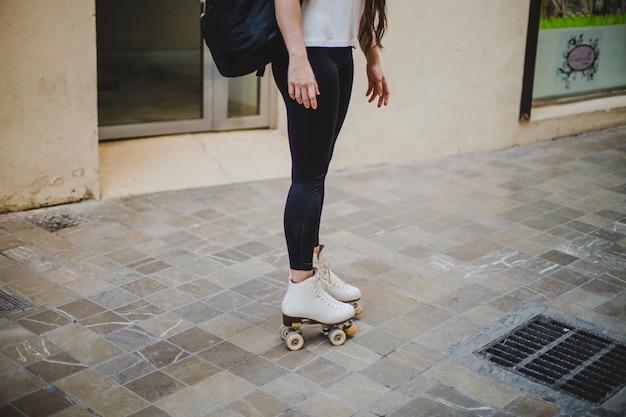 Woman wearing rollerskates standing on pavement
