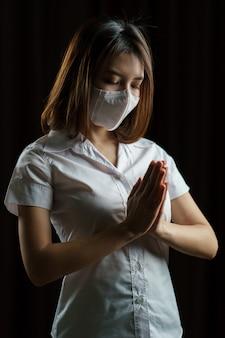 安全メガネとマスクを身に着けている女性。コロナウイルスの蔓延を防ぐため、こんにちはを意味する「タイワイ」または「ナマステ」を行って挨拶。