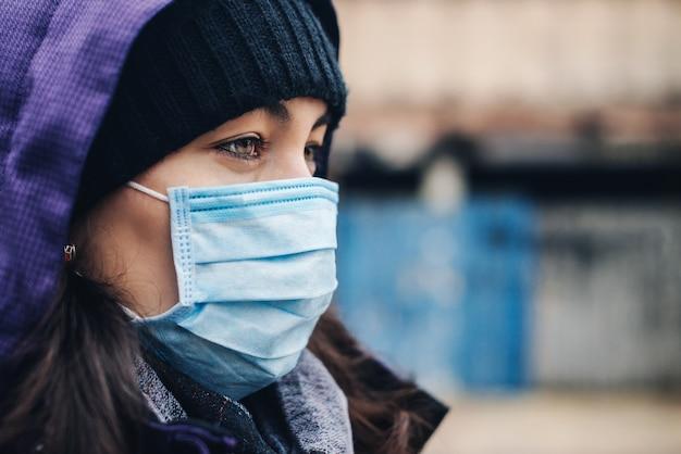 通りで防塵マスクを着用している女性。コロナウイルスの流行、封鎖。 covid19検疫。