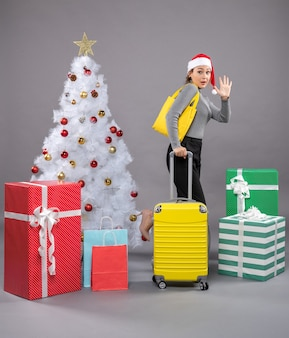 Woman wearing santa claus hat with luggage next to christmas tree