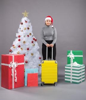 Donna che indossa il cappello di babbo natale con i bagagli accanto all'albero di natale
