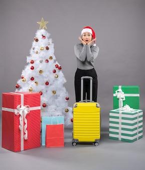 크리스마스 트리 옆에 짐을 싣고 산타클로스 모자를 쓴 여자
