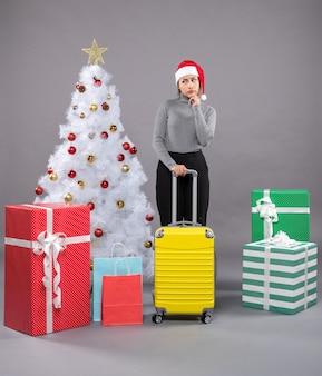 Женщина в шляпе санта-клауса с багажом рядом с елкой