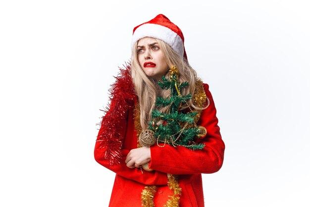 サンタの衣装のおもちゃの装飾の明るい背景を身に着けている女性