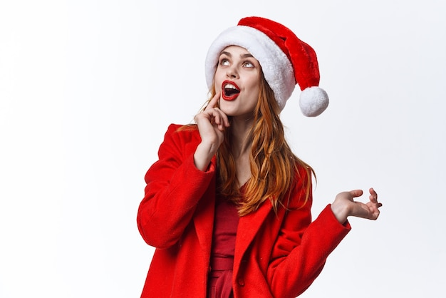 サンタの帽子をかぶった女性は、スタジオファッションのポーズを楽しんでいます。高品質の写真