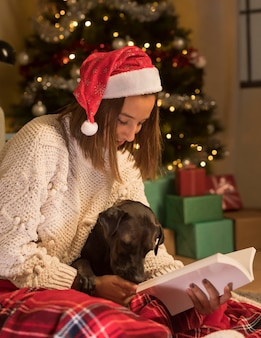 Женщина в шляпе санта-клауса на рождество и читает книгу со своей собакой