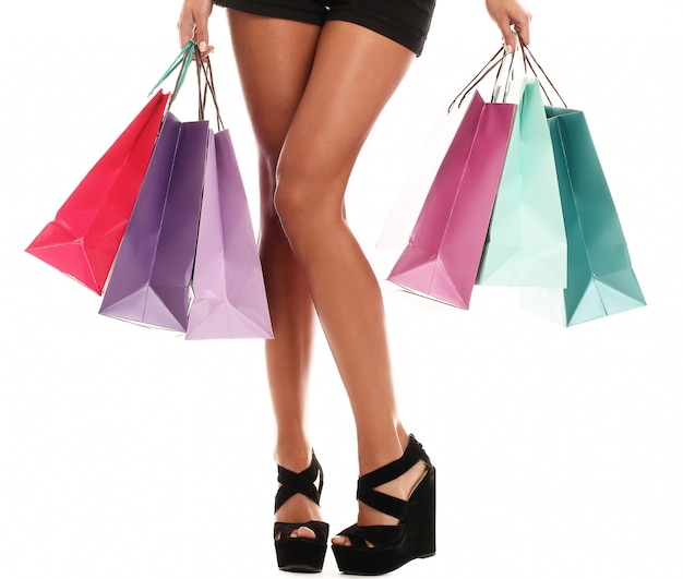 Woman wearing several colourful shopping bags