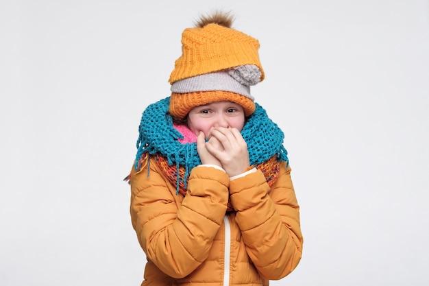 いくつかの暖かい冬の帽子とスカーフの爪をかむ女性