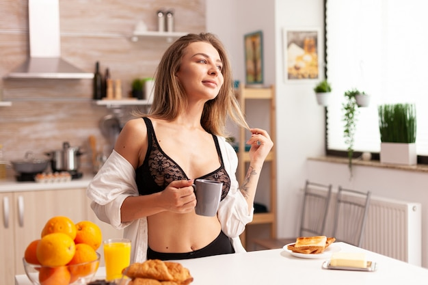 Woman wearing sexy bra during breakfast in home kitchen. young attractive woman with tattoos in seductive underwear holding cup of tea relaxing in the kitchen smiling.