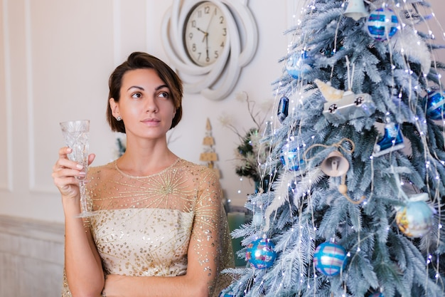 Woman wearing shiny golden evening christmas dress holding glass of champagne by bluenew year tree at home