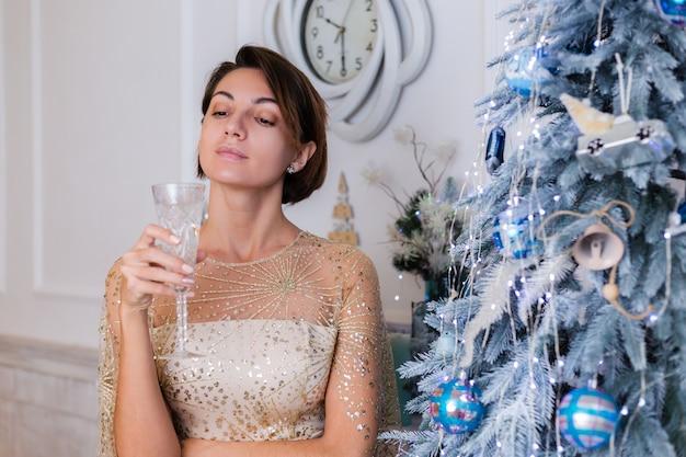 집에서 bluenew 년 나무에 의해 샴페인 잔을 들고 빛나는 황금 저녁 크리스마스 드레스를 입고 여자