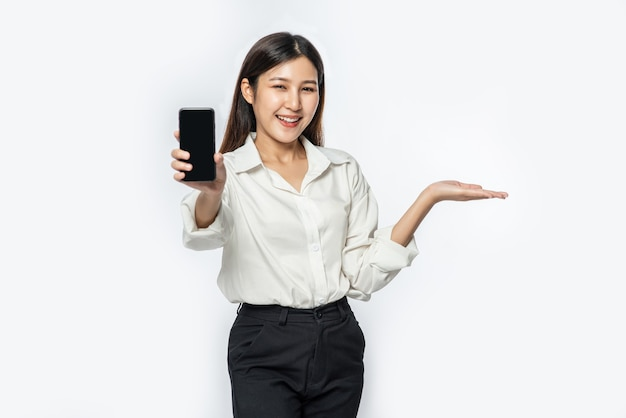 A woman wearing a shirt and holding a smartphone