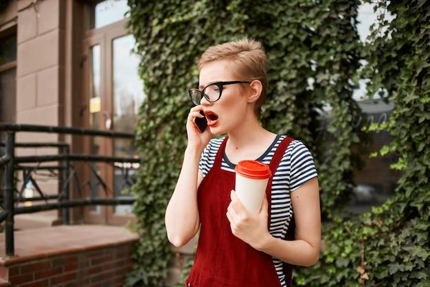 短い髪のグラスのコーヒーを屋外で着ている女性